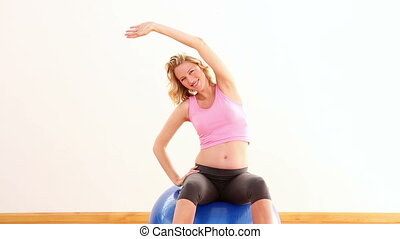 Pregnant blonde stretching on exercise ball