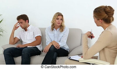 Unhappy couple talking with their therapist at therapy...