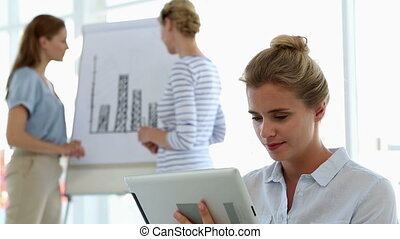Businesswoman using tablet with col