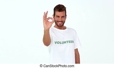 Handsome volunteer giving ok sign to the camera on white...