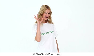 Pretty volunteer making ok sign to camera on white...