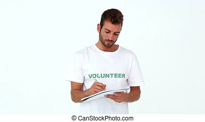 Handsome volunteer writing on notepad on white background