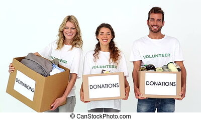Team of volunteers smiling at camera holding donations boxes...