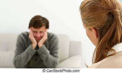 Young man sitting on sofa talking to his therapist at...