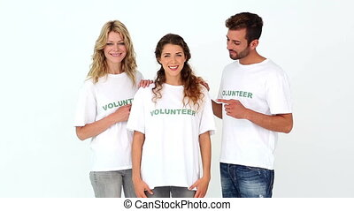 Team of volunteers smiling at camera on white background