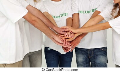 Team of volunteers putting hands together on white...