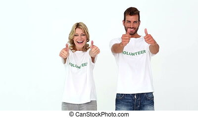 Two volunteers giving thumbs up to camera on white...