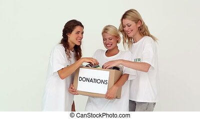 Team of volunteers holding donation box on white background