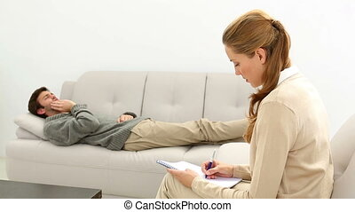 Young man lying on sofa talking to