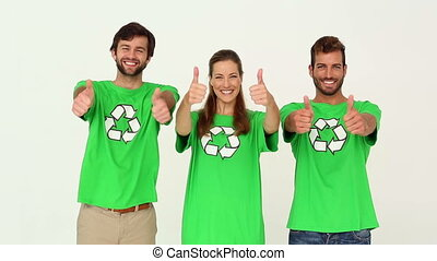 Team of environmental activists smiling at camera showing...