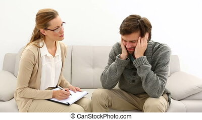 Young man talking with his therapist at therapy session