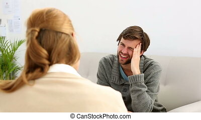 Young man sitting on sofa talking to therapist - Young man...