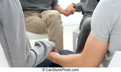 Rehab group sitting in a circle holding hands - Rehab group...