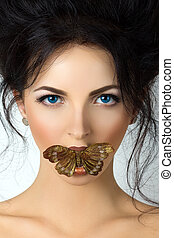 Young woman with mouth covered with butterfly. Concept of...