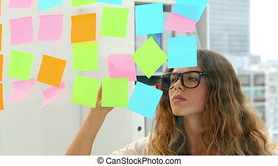Pretty designer looking at post its on window in creative...