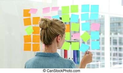Blonde designer looking at post its on window in creative...