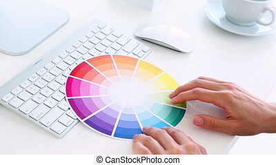 Graphic designer using colour wheel at his desk in creative...