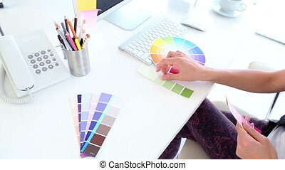 Graphic designer looking at colour samples in creative...