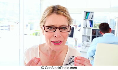 Angry businesswoman shouting at the camera in her office