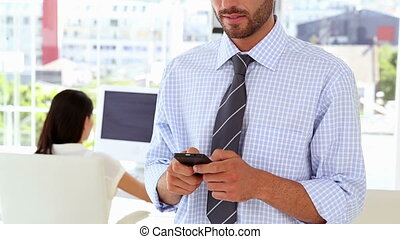 Man texting on phone while colleague works behind him in the...