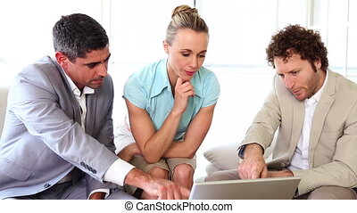 Business people working together on sofa with laptop in the...