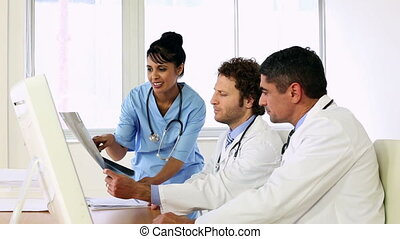 Doctors sitting at desk talking about xray with a nurse in...