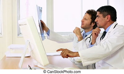 Doctors sitting at desk talking about xray in the office at...