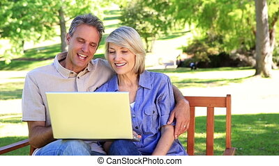 Affectionate couple sitting on park bench using laptop on a...