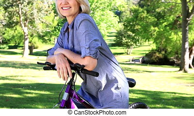 Smiling woman leaning on her bike - Smiling woman leaning on...
