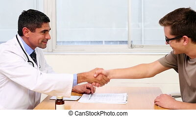 Doctor shaking hands with his patient in the office at the...