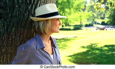Smiling woman leaning against a tree on a sunny day