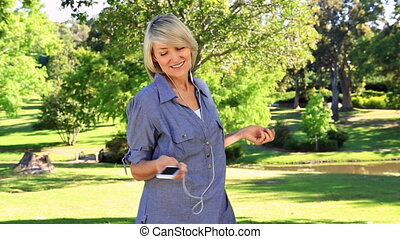 Smiling woman listening to music on a sunny day