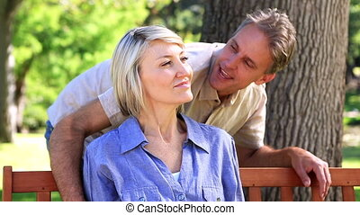 Happy man hugging his partner on park bench on a sunny day...