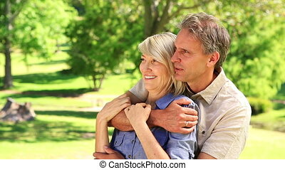 Happy couple embracing in the park on a sunny day