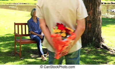 Man surprising his girlfriend with flowers in the park on a...