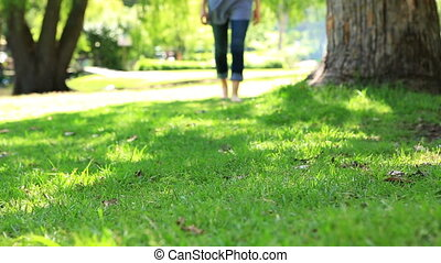 Woman walking barefoot on the grass on a sunny day