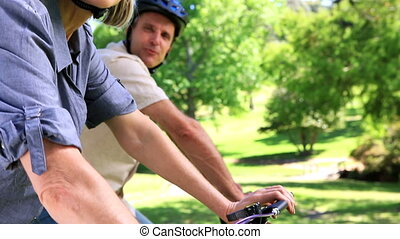 Happy couple going for a bike ride in the park on a sunny...