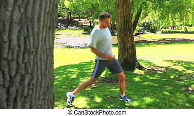 Man stopping his run to stretch in the park on a sunny day