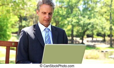 Businessman sitting on park bench using his laptop on a...