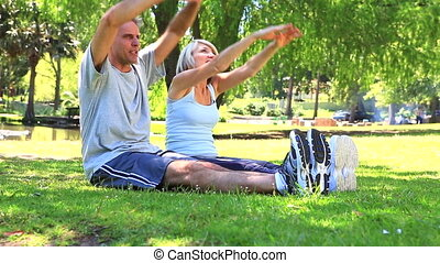 Couple stretching together in the park on a sunny day