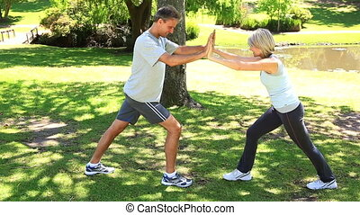 Couple leaning against each other to stretch in the park on...