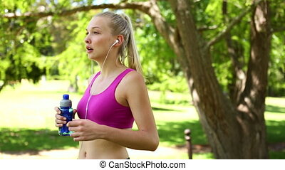 Blonde drinking water in the park - Fit blonde drinking...