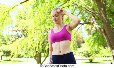 Fit blonde drinking water in the park on a sunny day