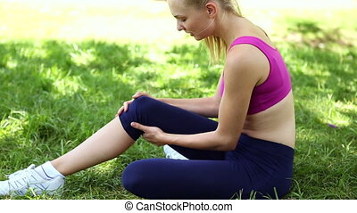 Injured fit blonde touching her knee on the grass on a sunny...