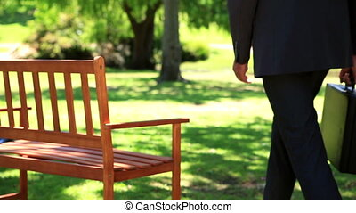 Businessman sitting down on park bench on a sunny day