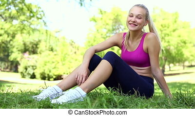 Fit blonde taking a break in the park sitting on the grass...