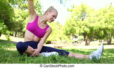 Fit blonde stretching on the grass