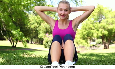 Fit blonde doing sit ups on the grass on a sunny day