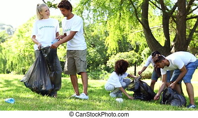 Happy volunteers picking up trash in the park on a sunny day...