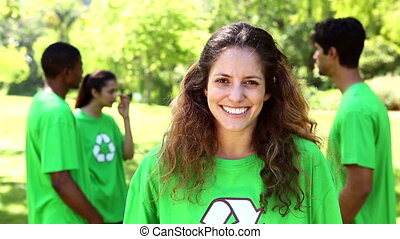 Happy environmental activist smiling at camera with team...